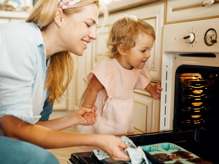 Smiling family cooking in an oven showing the need for appliance repairs