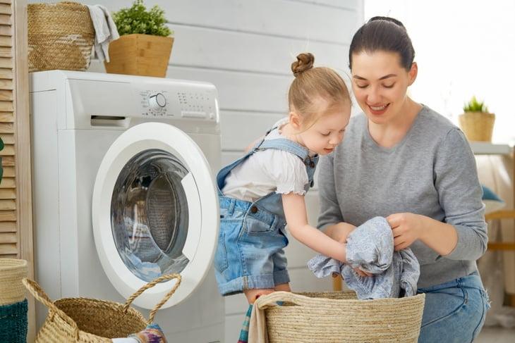 Smiling family folding dry laundry, representing dryer repairs